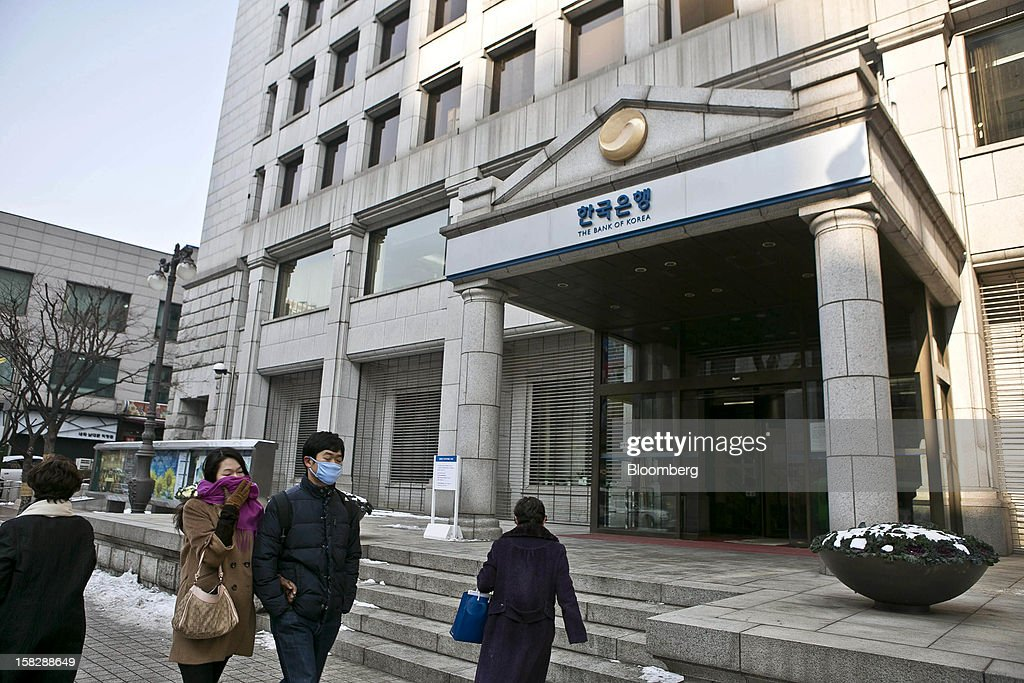 Pedestrians walk past the Bank of Korea headquarters in Seoul, South Korea, on Thursday, Dec. 13, 2012. The Bank of Korea held borrowing costs unchanged before next week's presidential election and after North Korea launched a rocket in defiance of international sanctions yesterday. Photographer: Jean Chung/Bloomberg via Getty Images