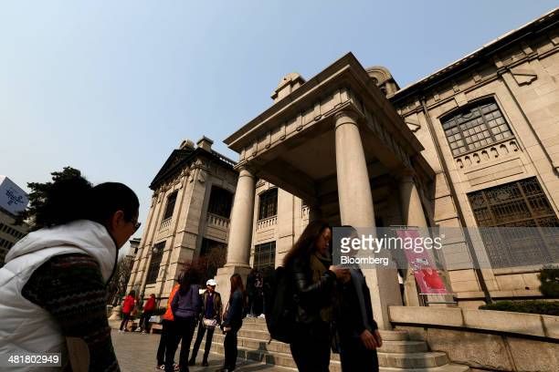 Pedestrians walk past the Bank of Korea museum at the central bank's headquarters in Seoul South Korea on Tuesday April 1 2014 Bank of Korea Governor...