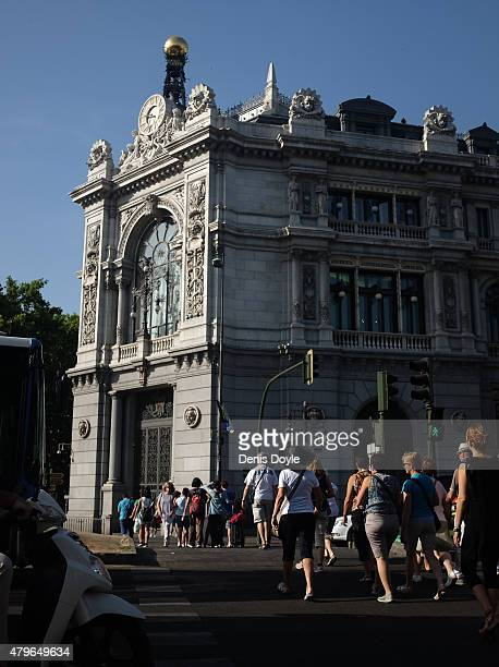 Pedestrians walk past the Bank of Spain headquarters a day after Greeks voted in a referendum to reject the European Union's latest Bailout terms for...