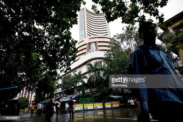 Pedestrians walk past the Bombay Stock Exchange in Mumbai India on Thursday July 14 2011 A day after three bombings killed at least 17 people in the...