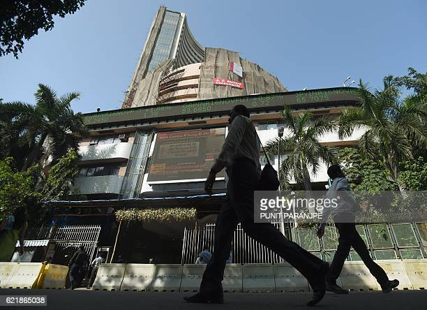 Pedestrians walk past the Bombay Stock Exchange in Mumbai on November 9 2016 Cash machines ran dry and stocks tumbled in India after Prime Minister...