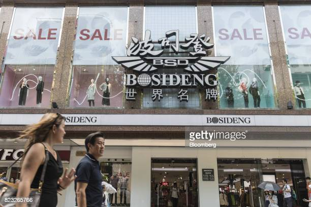 Pedestrians walk past the Bosideng International Holdings Ltd. Flagship clothing store in Shanghai, China, on Friday, July 14, 2017. Bosideng, a...
