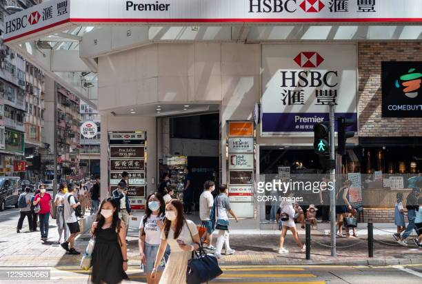 Pedestrians walk past the British multinational banking and financial services holding company HSBC Bank seen in Hong Kong