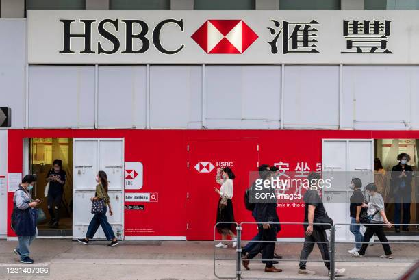 Pedestrians walk past the British multinational banking and financial services holding company, HSBC Bank seen in Hong Kong.