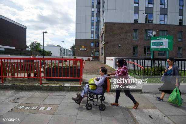 Pedestrians walk past the Burnham residential tower block on the Chalcots Estate in north London on June 23 2017 Tower blocks housing thousands of...