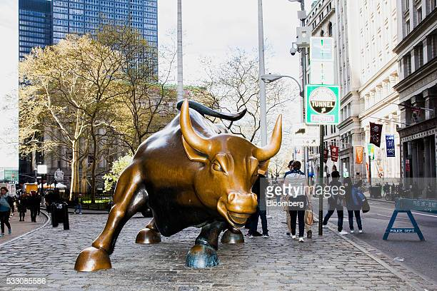 Pedestrians walk past the Charging Bull statue on Wall Street in New York US on Monday April 18 2016 US stocks rose with the SP 500 bouncing from a...