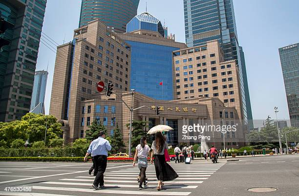 Pedestrians walk past the crossroad in front of the building of People's Bank of China in Shanghai Pudong. The consumer-price index increased 1.2...