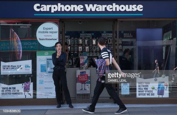 Pedestrians walk past the entrance to a Carphone Warehouse mobile phone shop in London on September 17 2018