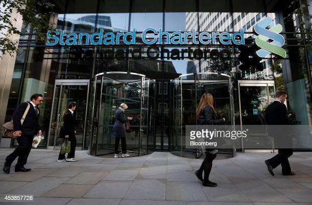 Pedestrians walk past the entrance to Standard Chartered Plc's headquarters in London UK on Wednesday Aug 20 2014 Standard Chartered agreed to pay...