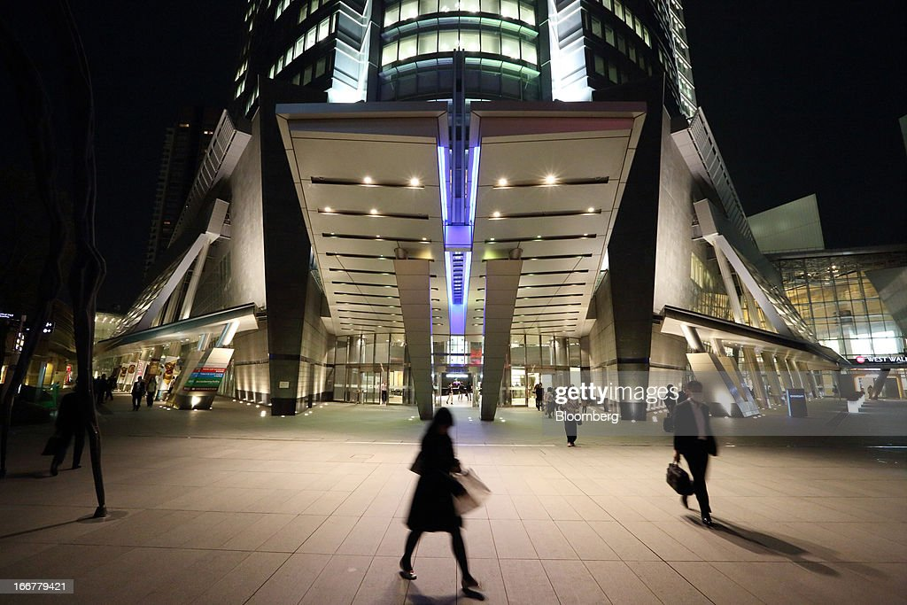 Pedestrians walk past the entrance to the Roppongi Hills Mori Tower, operated by Mori Building Co., at night in Tokyo, Japan, on Tuesday, April 17, 2013. While financial firms have cut staff in Japan, technology companies have boosted hiring, and as bankers vacated offices at Roppongi Hills, companies including Google Inc. and Lenovo Group Ltd. moved in. As early as this month, Apple Inc. will also make the complex its home in Japan, two people familiar with the plan said in January. Photographer: Tomohiro Ohsumi/Bloomberg via Getty Images