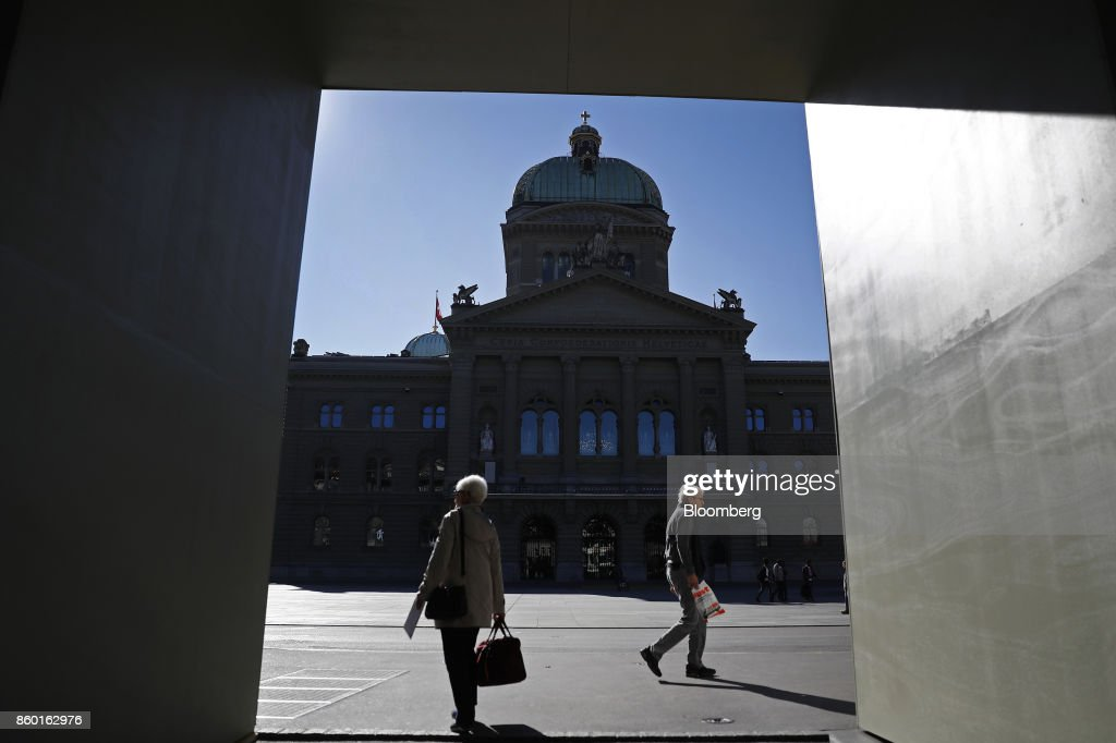 Pedestrians walk past the Federal Palace, Switzerland's parliament building, in Bern, Switzerland, on Wednesday, Oct. 11, 2017. Big banks are pushing back against Swiss plans to relax rules that are making it hard for small financial firms to compete against the likes of UBS Group AGand Credit Suisse Group AG. Photographer: Stefan Wermuth/Bloomberg via Getty Images