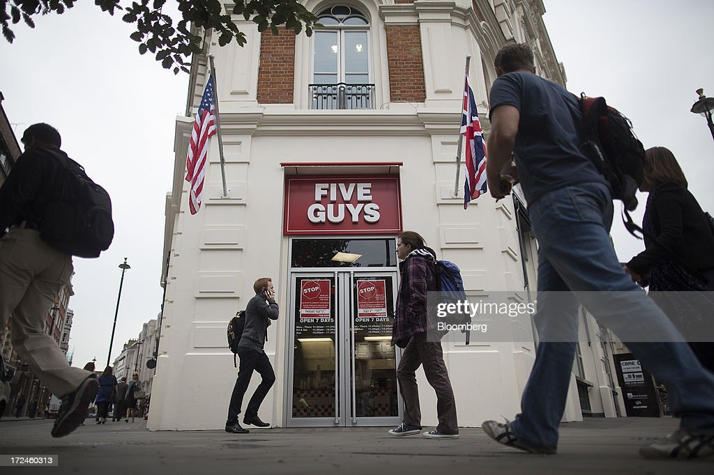 Pedestrians walk past the first U.K. outlet of U.S. burger restaurant chain Five Guys in London, U.K., on Tuesday, July 2, 2013. Five Guys, which is set to open its first U.K. store in Covent Garden on July 4, is a family outfit that started in Washington, D.C., in 1986, and has expanded to more than 1,000 locations in the U.S. and Canada. Photographer: Simon Dawson/Bloomberg via Getty Images