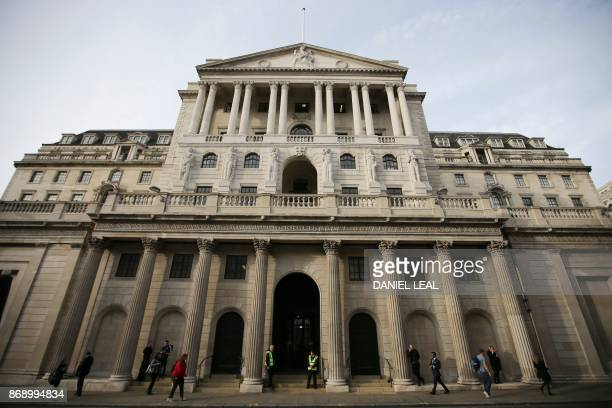 Pedestrians walk past the front of The Bank of England in the City of London on November 1 2017 The Bank of England on guard against soaring...