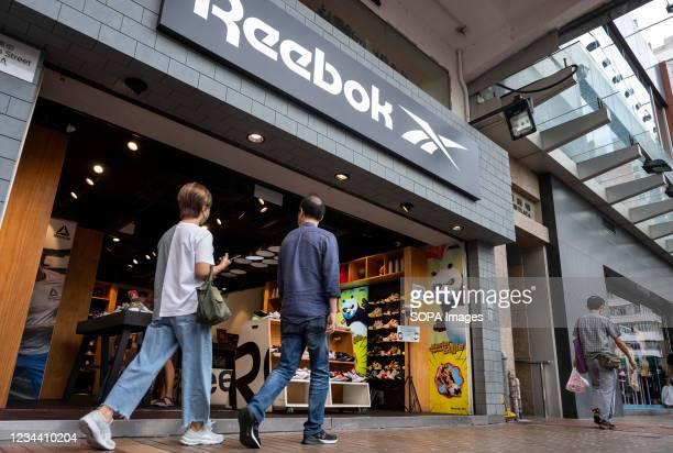 Pedestrians walk past the German multinational footwear company brand Reebok store is seen in Hong Kong.