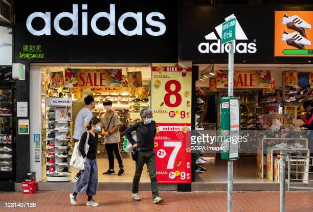 Pedestrians walk past the German multinational sportswear clothing brand, Adidas store seen in Hong Kong.