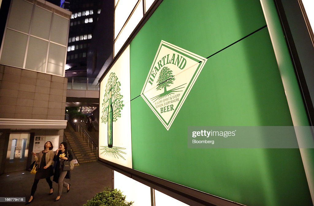 Pedestrians walk past the Heartland bar at the Roppongi Hills complex, operated by Mori Building Co., at night in Tokyo, Japan, on Tuesday, April 17, 2013. While financial firms have cut staff in Japan, technology companies have boosted hiring, and as bankers vacated offices at Roppongi Hills, companies including Google Inc. and Lenovo Group Ltd. moved in. As early as this month, Apple Inc. will also make the complex its home in Japan, two people familiar with the plan said in January. Photographer: Tomohiro Ohsumi/Bloomberg via Getty Images
