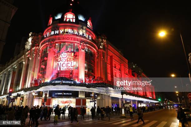 Pedestrians walk past the illuminated entrance to the BHV Marais in Paris on November 15 as the Christmas lights were turned on at the iconic store...