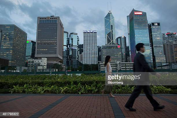 Pedestrians walk past the Legislative Council Complex left the Chinese People's Liberation Army Forces Hong Kong Building third left Lippo Center...