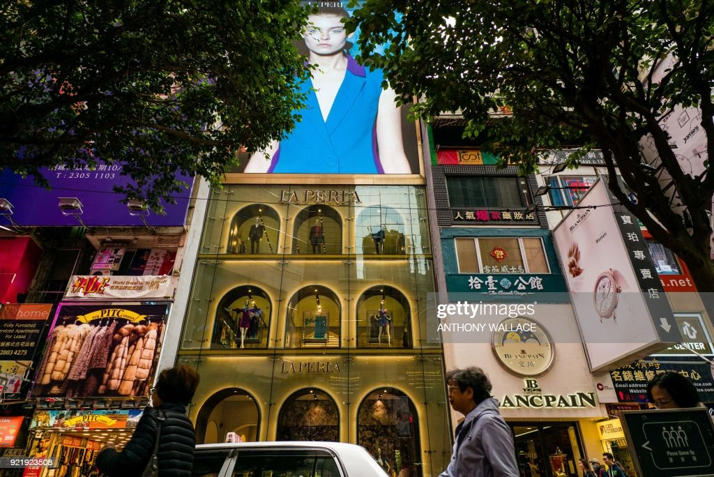 Pedestrians walk past the local flagship store of Italian luxury lingerie brand La Perla (C) in the Causeway Bay district of Hong Kong on February 21, 2018. /
