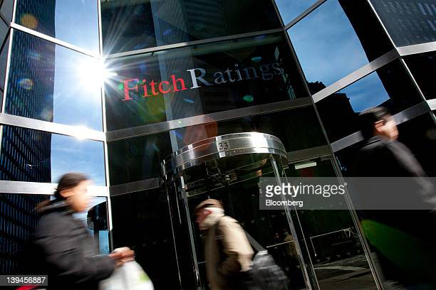 Pedestrians walk past the logo for Fitch Ratings Ltd outside their offices in New York US on Tuesday Feb 21 2012 Fitch provides the world's credit...