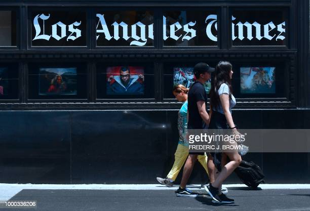 Pedestrians walk past the Los Angeles Times office building in downtown Los Angeles California on July 16 2018 The newspaper is preparing a legal...
