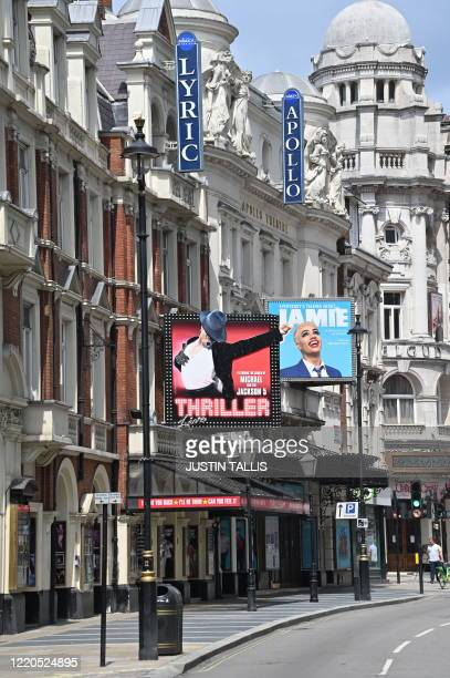 Pedestrians walk past the Lyric and Apollo Theatres, which would be showing 'Thriller Live', and 'Jamie', but are closed down as part of the COVID-19...