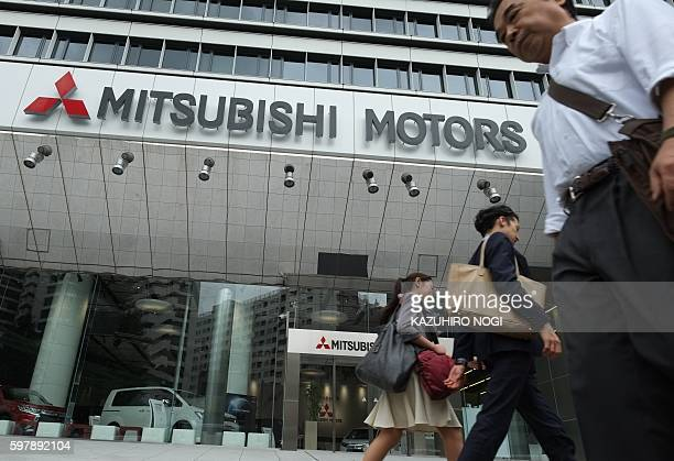 Pedestrians walk past the Mitsubishi Motors headquarters in Tokyo on August 30 2016 / AFP / KAZUHIRO NOGI