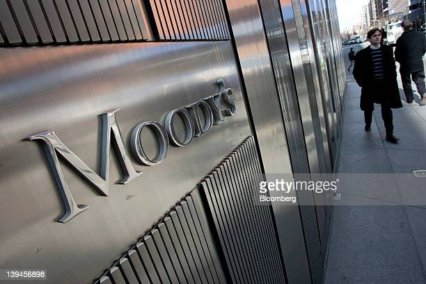 Pedestrians walk past the Moody's Investors Service Inc logo displayed outside of the company's headquarters in New York US on Tuesday Feb 21 2012...