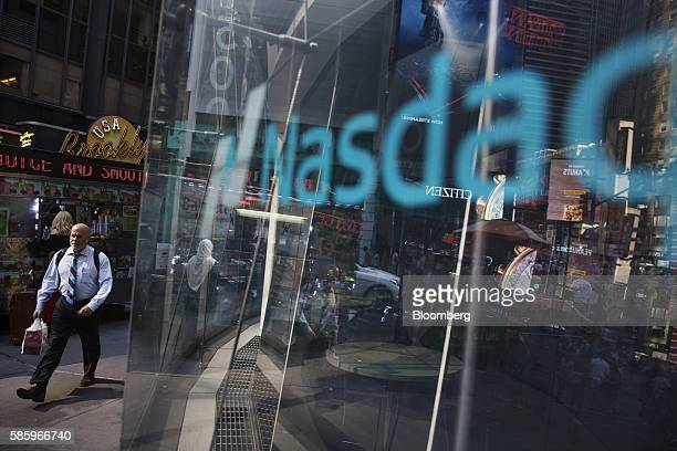Pedestrians walk past the Nasdaq MarketSite in New York US on Thursday Aug 4 2016 First Hawaiian Inc jumped in its trading debut after its owner...