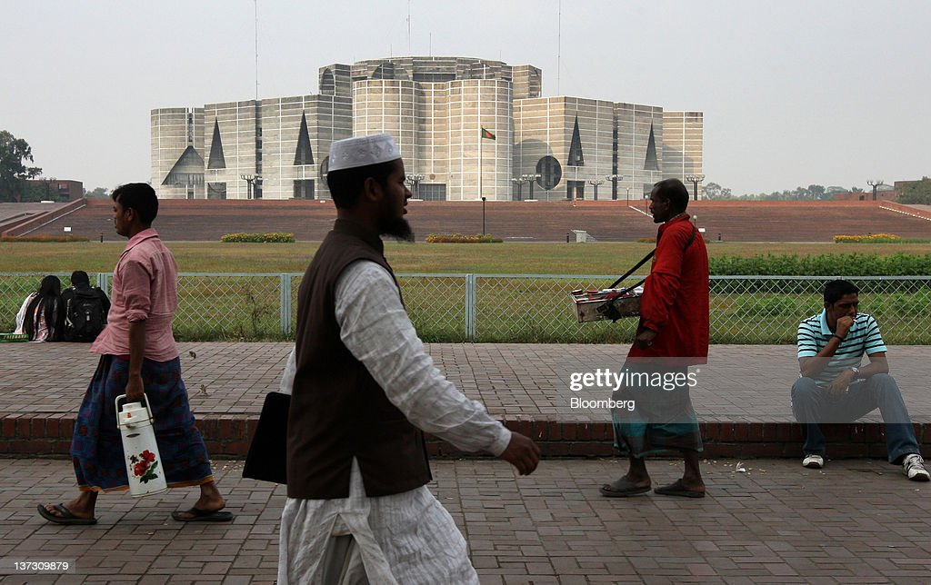 Pedestrians walk past the national assembly building in Dhaka, Bangladesh, on Tuesday, Jan. 10, 2012. Bangladesh's central bank this month raised interest rates for the second time in four months to curb inflation that has exceeded 9 percent since the start of 2011. Photographer: Tomohiro Ohsumi/Bloomberg via Getty Images