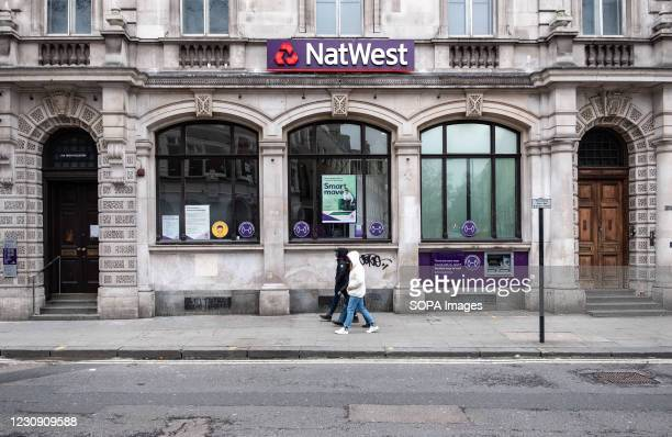 Pedestrians walk past the National Westminster Bank, commonly known as NatWest, a major retail and commercial bank in the United Kingdom.
