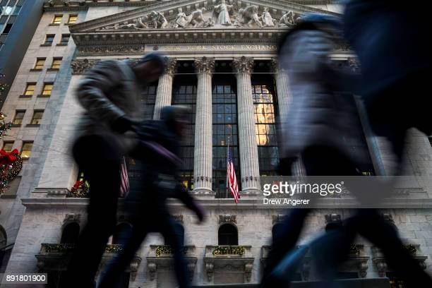 Pedestrians walk past the New York Stock Exchange after the closing bell December 13 2017 in New York City The Dow Jones industrial average closed at...