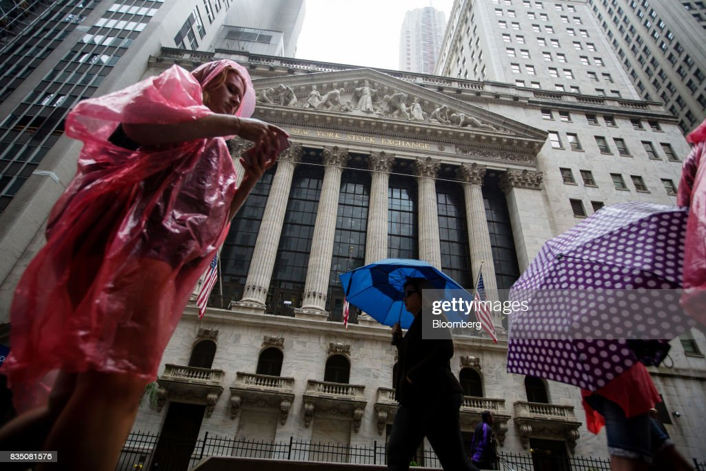 Pedestrians walk past the New York Stock Exchange (NYSE) in New York, U.S., on Friday, Aug. 18, 2017. Stocks were mixed and the S&P 500 Index turned higher as investors digested the political upheaval in the U.S. and the latest terrorist attack in Europe. Photographer: Michael Nagle/Bloomberg via Getty Images