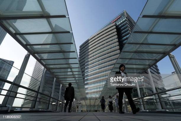 Pedestrians walk past the Nissan Motor Co. Headquarters on March 12, 2019 in Yokohama. Japan. Nissan, Renault SA and Mitsubishi Motors Corp....