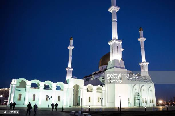 Pedestrians walk past the NurAstana Mosque at night in Astana Kazakhstan on Saturday April 14 2018 Kazakhstan's gross domestic product for the...