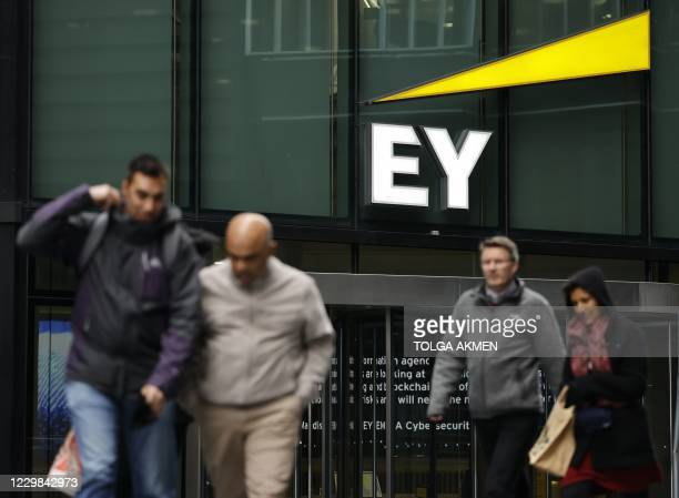 Pedestrians walk past the offices of accounting and auditing firm EY, formerly Ernst & Young, in London on November 20, 2020. - Britain's audit...