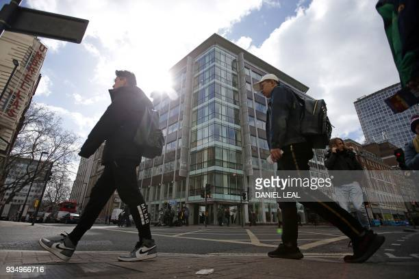 Pedestrians walk past the offices of Cambridge Analytica in central London on March 20 2018 Facebook shares plunged Monday as the social media giant...