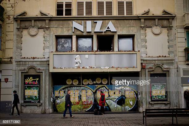 Pedestrians walk past the old facade of the cinema Niza in Barcelona Spain on 11 Feb 2016 A few meters from the Passion facade of the Sagrada Familia...