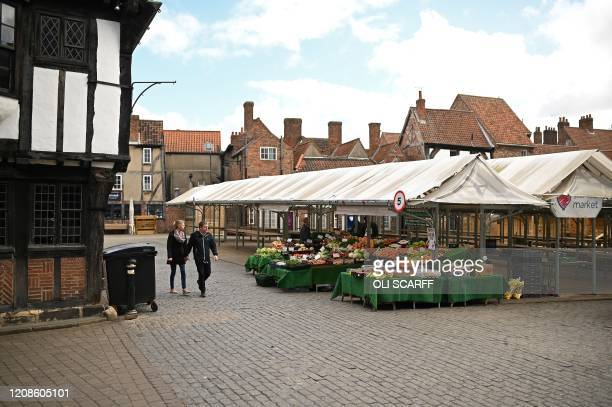 Pedestrians walk past the only stall open a fruit and vegetable stall at Newgate Market in York in northern England on March 30 as life in Britain...
