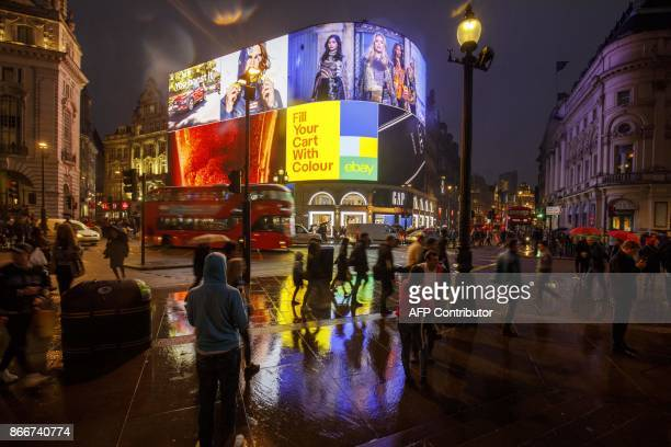 Pedestrians walk past the Piccadilly Circus advertisement screens in London on October 26, 2017 after they were switched back on after a major...