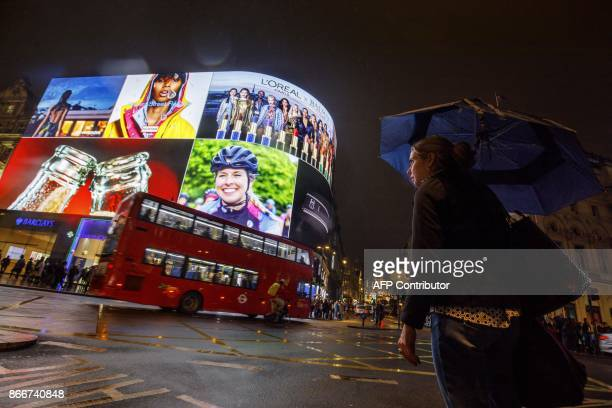 Pedestrians walk past the Piccadilly Circus advertisement screens in London on October 26 2017 after they were switched back on after a major...