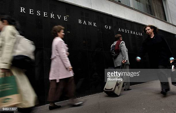 Pedestrians walk past the Reserve Bank of Australia headquarters in Sydney Australia on Wednesday August 2 2006 Australia's central bank raised its...