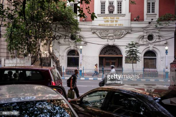 Pedestrians walk past the Reserve Bank of India's building in the BBD Bagh area of Kolkata India on Thursday May 25 2017 India is scheduled to...