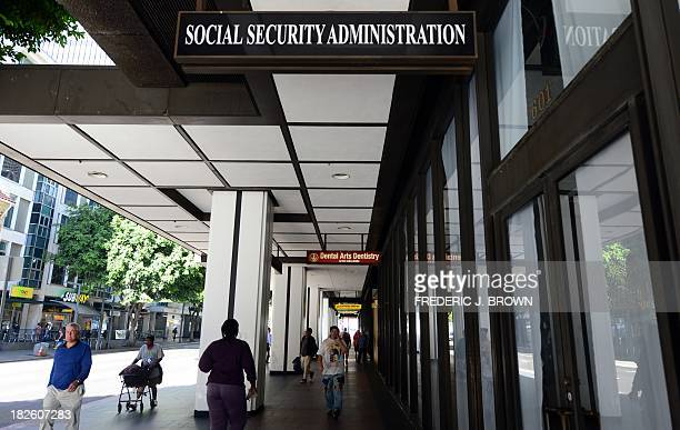 Pedestrians walk past the Social Security Administration office in downtown Los Angeles, on October 1, 2013 in California. US monuments closed,...