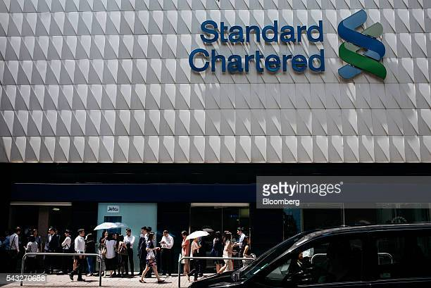 Pedestrians walk past the Standard Chartered Plc logo at the bank's headquarters building in the Central district of Hong Kong China on Monday June...