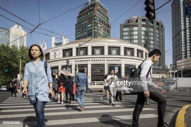 Pedestrians walk past the Starbucks Corp Reserve Roastery store in Shanghai China on Friday May 11 2018 Starbucksis laying out an ambitious plan to...