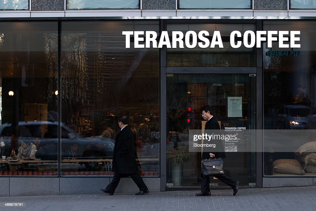 Pedestrians walk past the Terarosa Coffee shop in Seoul, South Korea, on Tuesday, Feb. 4, 2014. South Korea is Asias fastest-growing market for arabica coffee, the mild-tasting beans used in premium blends. Photographer: SeongJoon Cho/Bloomberg via Getty Images
