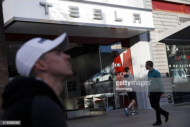 Pedestrians walk past the Tesla Motors Inc store on the Third Street Promenade in Santa Monica California US on Wednesday March 30 2016 Tesla Motor...