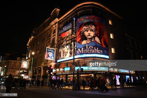 Pedestrians walk past the the Sondheim Theatre, where a performance of Les Miserables will be shown in London on December 15 before the theatre...