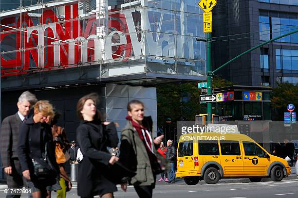 Pedestrians walk past the Time Warner Inc Center in New York on October 23 2016 ATT unveiled a megadeal for Time Warner that would transform the...